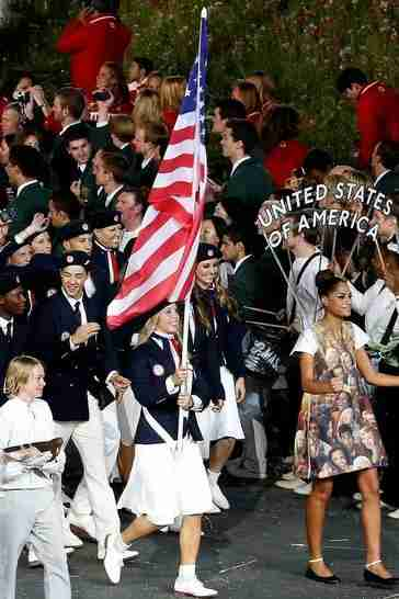 Mariel Zagunis, a fencer, carries the U.S. flag into the Olympic Games opening ceremony.