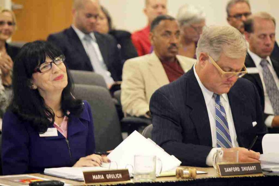 Board member Maria Grulich (L) sits next to Valencia College president Dr. Sandy Shugart (R).