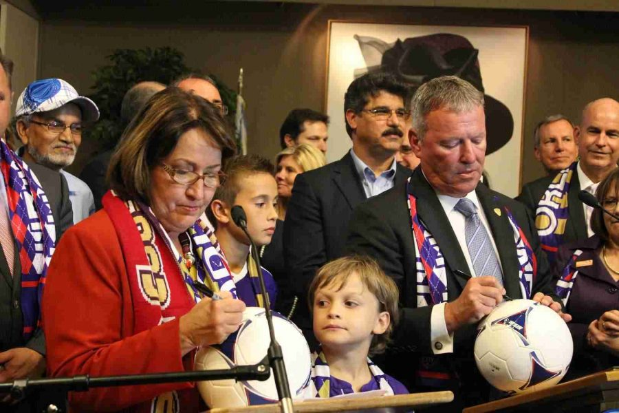 Orange County Mayor Teresa Jacobs (left) and City of Orlando Mayor Buddy Dyer sign soccer balls in honor of the vote.