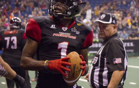 Larry Brackins throws a game ball into the stands after his third touchdown of the night.