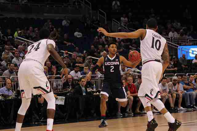 UConn freshman Jalen Adams (center) hit a three-quarter court shot in the third overtime to keep the Huskies alive.