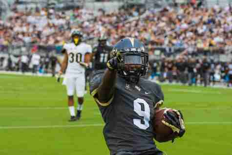 Adrian Killins, Jr. points to the crowd after scoring a touchdown.