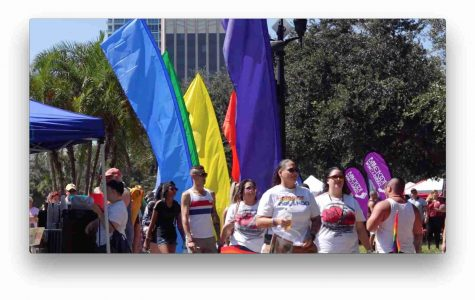 marchers in front of rainbow flags at Come Out With Pride event