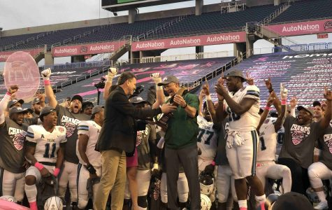 Tulane Head Coach Willie Fritz (center) receives the Cure Bowl trophy alongside the game MVP Darius Bradwell (right) (Bryony Deighton)