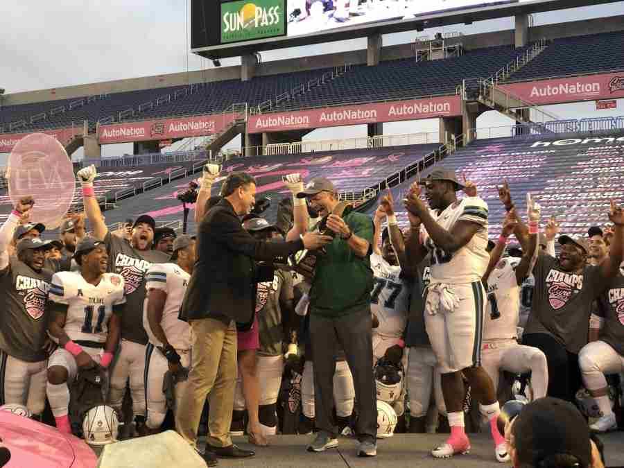 Tulane+Head+Coach+Willie+Fritz+%28center%29+receives+the+Cure+Bowl+trophy+alongside+the+game+MVP+Darius+Bradwell+%28right%29+%28Bryony+Deighton%29