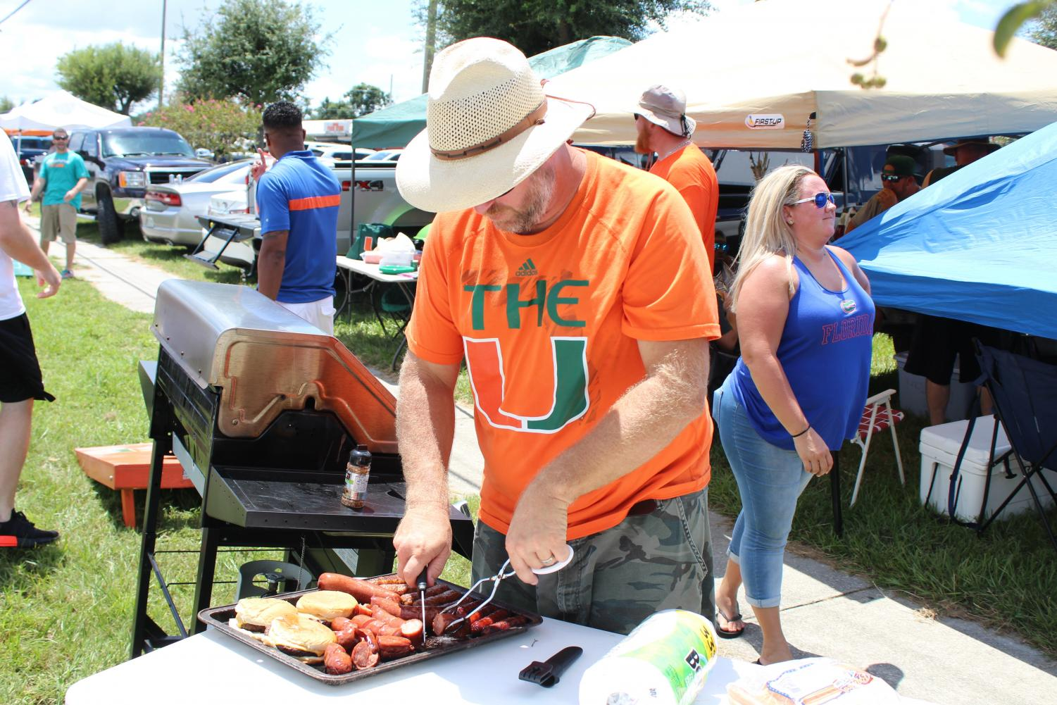 Trent Hopper prepares food during the tailgate.
