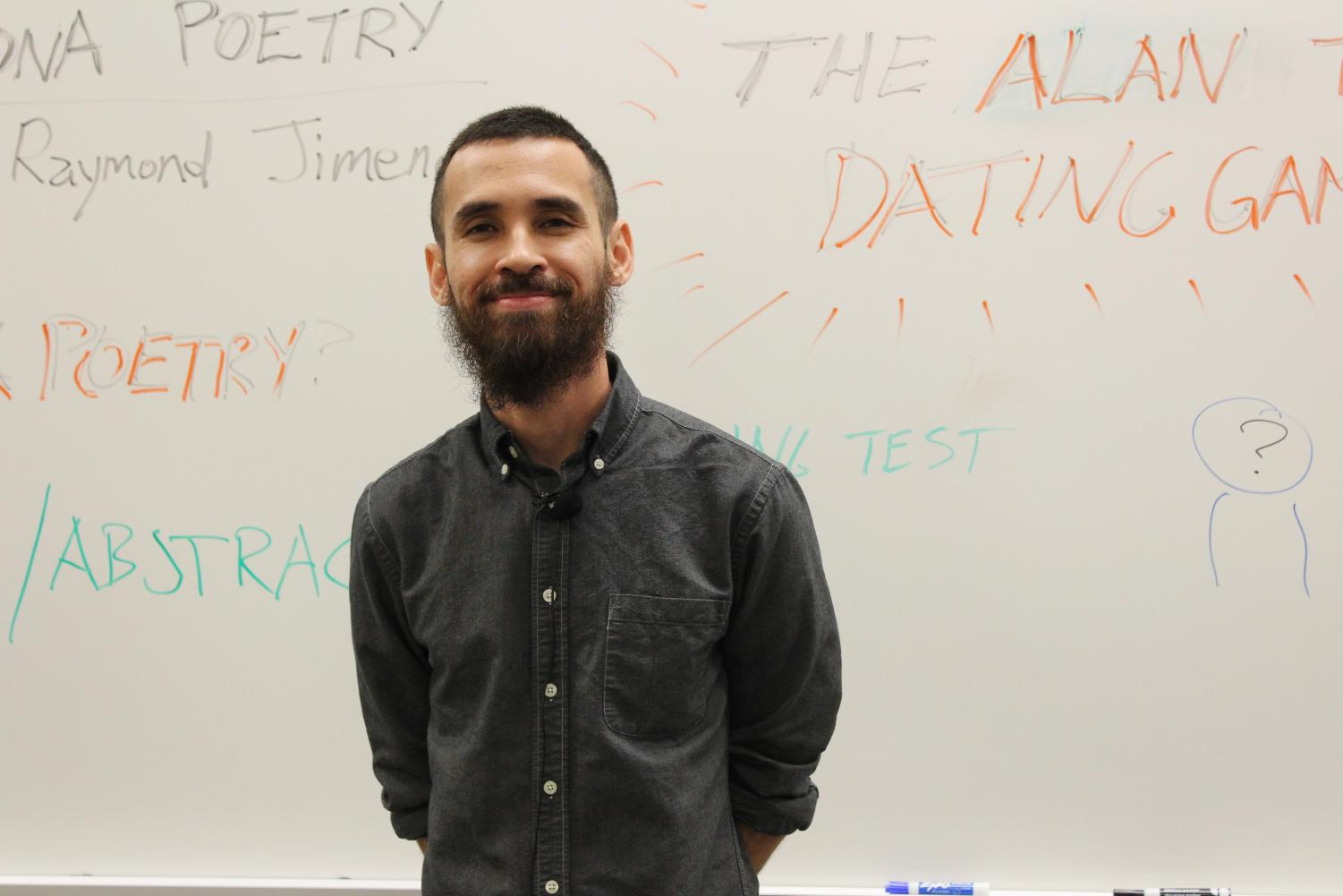 Raymond Jimenez uses the white board in Building 8, Room 101 to inform attendees about poetry.