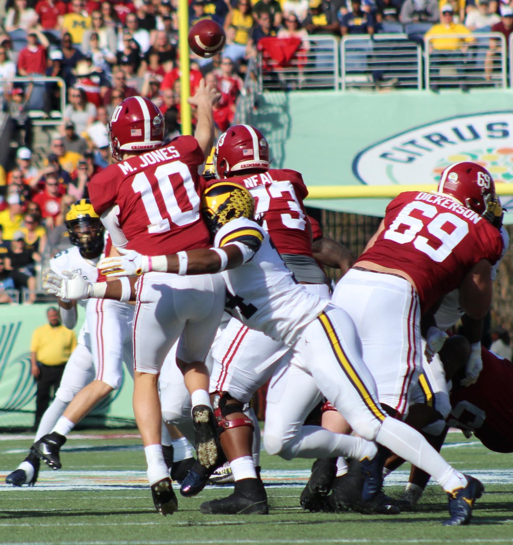 Alabama Quarterback Mac Jones (10) is able to get a pass away.