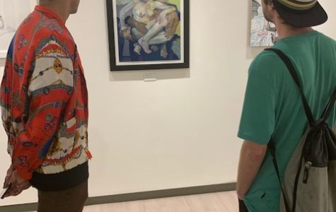 Two students gaze at one of Lucey's pieces at Thursdays exhibit opening.