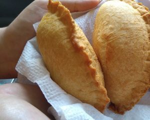 Empanadas being served on a paper towel.