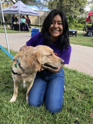 Dayane Villatoro greeting an emotional support dog during FallOh Your Path's 2019 stress relief event.