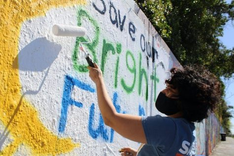 Alondra Arce, 20, a UF sustainability sophomore, paints a mural that says Save Our Bright Futures on Sunday, March 7, 2021. Arce recruited student volunteers to help her create the mural along 34th Street in Gainesville to raise awareness about Senate Bill 86, which would limit some students access to state funding for college if passed.
