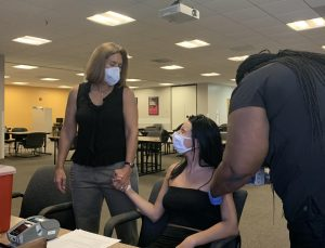 Emma Blount, 19, Valencia College student, receives the Pfizer vaccine at the East Campus vaccination site while Professor Rebecca Newman offers emotional support.